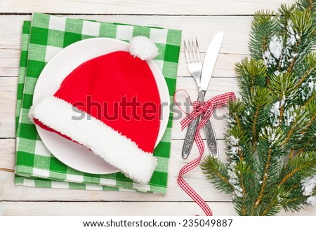 Santa hat on plate, silverware and christmas tree. View from above over white wooden table background - stock photo