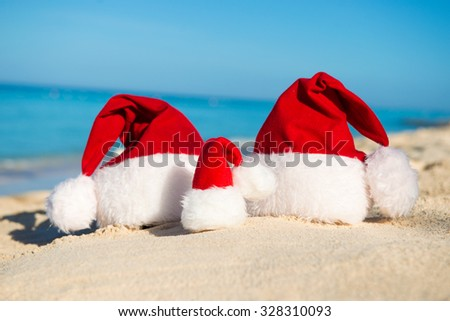 Santa hats on sandy beach  - concept of New Year family holiday with the children on the sea. - stock photo