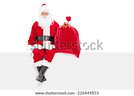 Santa holding a bag of presents seated on a panel isolated on white background - stock photo