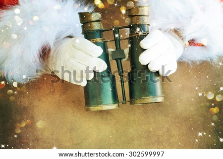 Santa holding binocular - stock photo