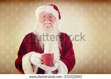 Santa holds a red cup against room with wooden floor - stock photo