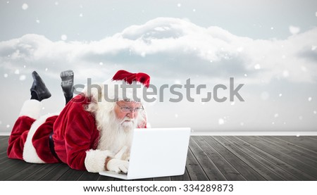 Santa lies in front of his laptop against clouds in a room - stock photo