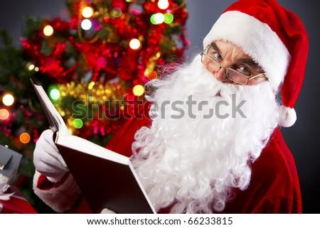 Santa looking at camera while reading a book - stock photo