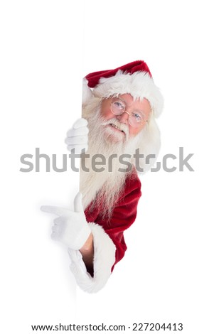 Santa looks out behind a wall on white background - stock photo