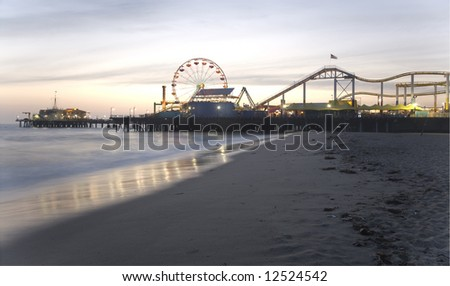 Santa Monica Beach, Santa Monica, CA May 3, 2008:  Horizontal image of the Santa Monica Pier with the prominent Ferris wheel and other thrill rides taken at dusk. - stock photo