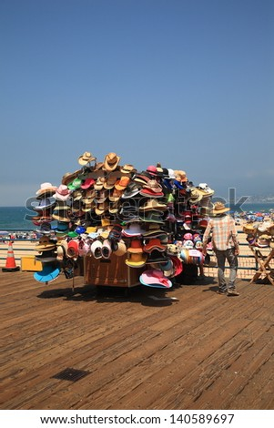 SANTA MONICA, CALIFORNIA - JULY 1: A vendor selling beach appropriate hats on the pier on July 1, 2012 in Santa Monica, California. The pier opened in 1909 and now has an aquarium and a carousel. - stock photo