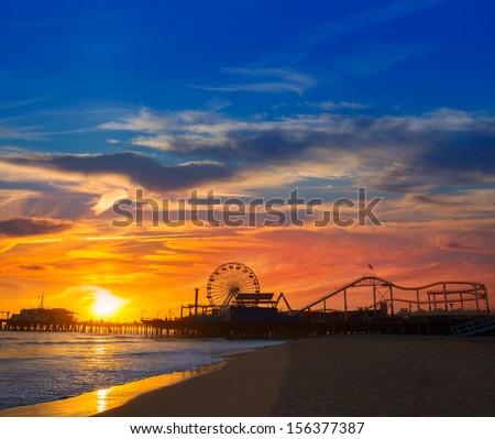 Santa Monica California sunset on Pier Ferris wheel and reflection on beach wet sand - stock photo