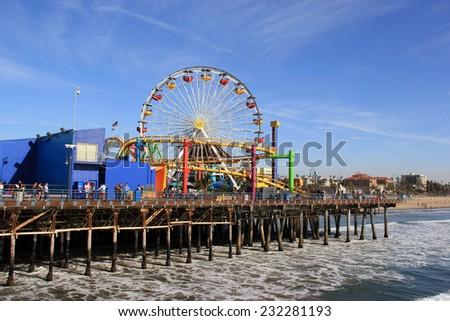 Santa Monica, California, USA - November 16, 2014: The Santa Monica Pier, containing shops, restaurants and an amusement park with the world's only solar powered Ferris wheel. - stock photo