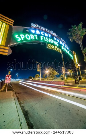 SANTA MONICA - JAN 14, 2015: Santa Monica Yacht Harbor Sign in Los Angeles California at Night with Long Exposure Car Light Streak. Santa Monica is a beachfront city in Los Angeles California. - stock photo