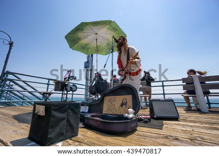 SANTA MONICA, USA - JUNE 19: street musician sings and plays guitar dressed in Jesus costume on the Santa Monica pier on June 19, 2016. - stock photo