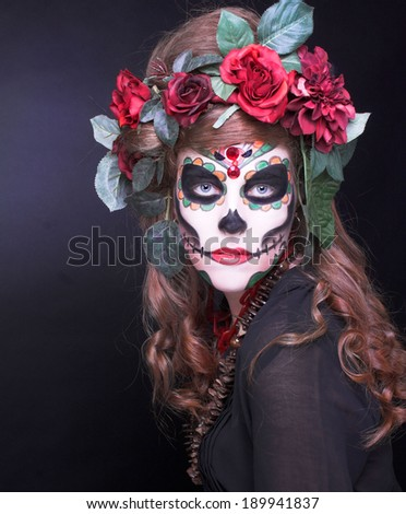 Santa Muerte. Young woman with artistic visage and with roses in her hair/ - stock photo