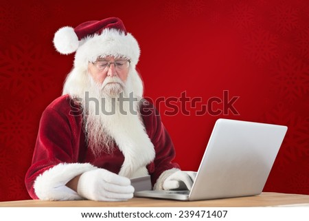 Santa pays with credit card on a laptop against red background - stock photo