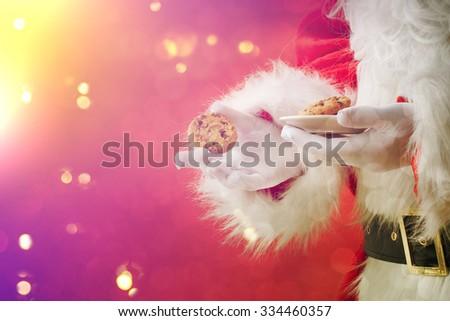 Santa picking cookie  - stock photo