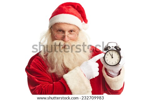 Santa pointing at alarm clock showing five minutes to xmas - stock photo