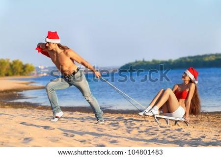 Santa pulling Sexy Santa girl on a sled at the beach.(concept: Tropical winter fun) - stock photo
