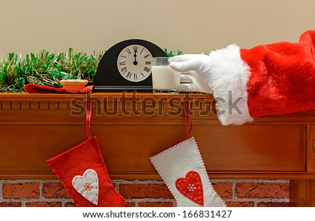 Santa reaching for his glass of milk at midnight on Christmas Eve - stock photo