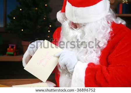 "Santa reads his ""letters to santa"" - stock photo"