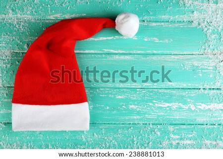 Santa red hat and snowflakes on color wooden background - stock photo