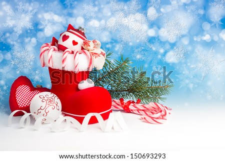 Santa's boot and Xmas canes on blue winter background - stock photo