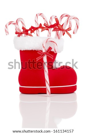 Santa's boot with candy canes on white background - stock photo
