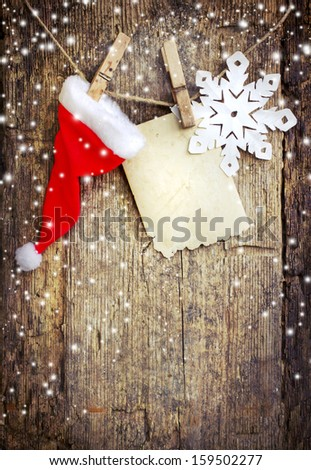 Santa's hat and snowflakes  hanging on a desaturated grunge wood background. - stock photo
