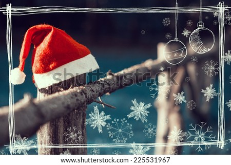 Santa's hat on the wooden fence in the peaceful, inviting, rural environment ideal for holiday season - stock photo