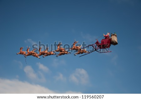 Santa's Sleigh flying above the city during Christmas - stock photo