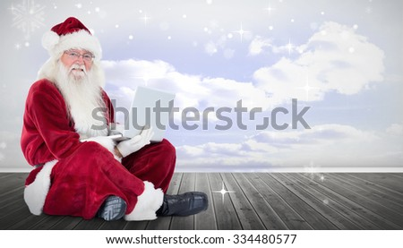 Santa sits and uses a laptop against clouds in a room - stock photo