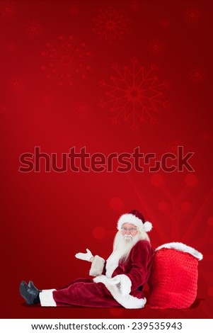 Santa sits leaned on his bag and has no clue against red background - stock photo