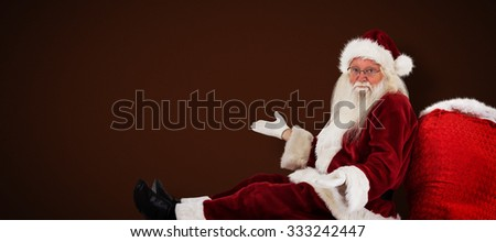 Santa sits leaned on his bag and has no clue against white background with vignette - stock photo