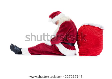 Santa sits leaned on his bag on white background and sleeps - stock photo