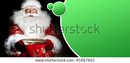 Santa sitting at the Christmas room and looking into the sack. Blank graphic balloon with lots of copyspace for your text and logo overhead - stock photo
