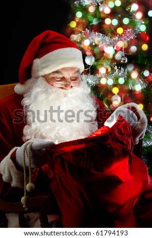 Santa sitting at the Christmas tree and looking into the sack - stock photo