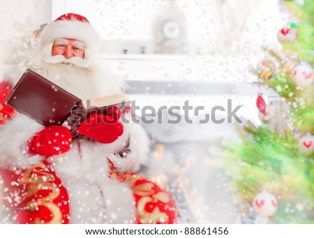 Santa sitting at the Christmas tree, near fireplace and reading a book. Indoors. Magic snowy poster - stock photo