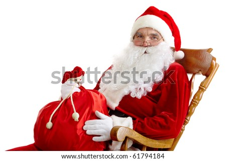Santa sitting in the armchair and holding a sack isolated on white - stock photo