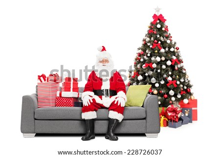 Santa sitting on a sofa by a Christmas tree isolated on white background - stock photo