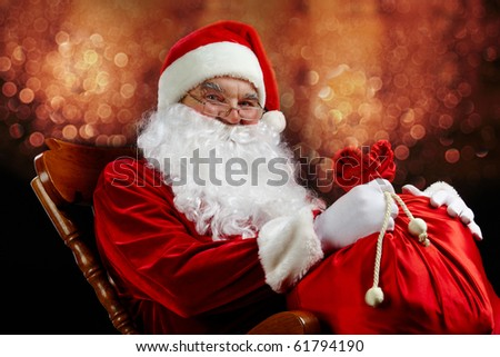 Santa sitting with a sack against glaring lights - stock photo