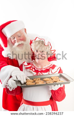 Santa steals a warm cookie from Mrs Claus tray. - stock photo