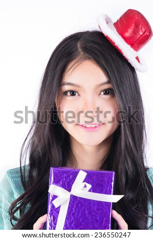 Santa woman holding gift wearing Santa hat. Christmas woman portrait of a cute, beautiful smiling mixed Asian / Caucasian model. Isolated on white background.  - stock photo