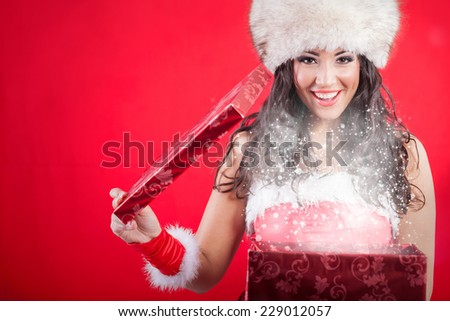 Santa woman in hat opening box with present,red background - stock photo