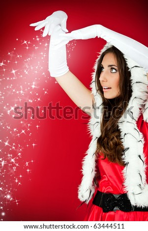 santa woman watching the snowflakes fall from her hands - stock photo