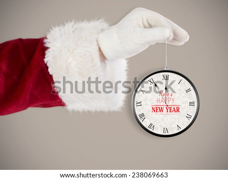 Santas hand is holding a Christmas bulb against grey background with vignette - stock photo
