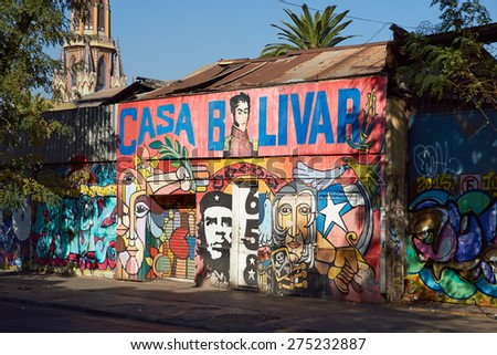 SANTIAGO, CHILE - APRIL 17, 2015: Colourful murals decorating a street in Barrio Brasil, Santiago, Chile. Steeple of the historic church, Iglesia Corpus Dominco, in the background. - stock photo