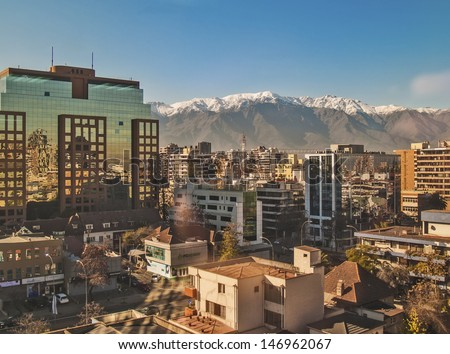 SANTIAGO, CHILE - JUNE 24:  Financial and residential district Las Condes with The Andes mountains covered with snow on background on June 24, 2013 in Santiago, Chile - stock photo