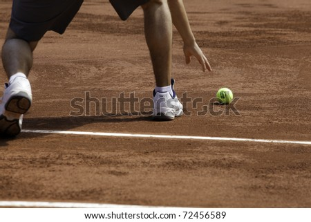 SANTIAGO, CHILE - MAR 4: A boys takes a ball from the groundduring the match of Chile against  USA  valid for the Davis Cup. March 4, 2011 in Santiago Chile. - stock photo
