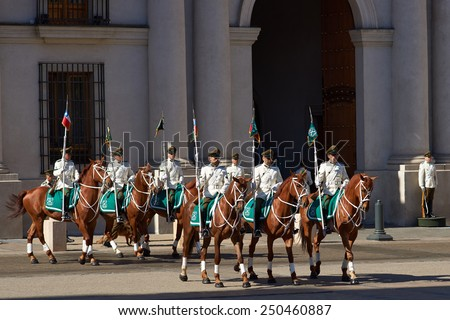 SANTIAGO, CHILE - NOVEMBER 6, 2014: Carabineros de Chile in white summer uniform performing the Changing of the Guard ceremony outside La Moneda in Santiago, capital of Chile - stock photo