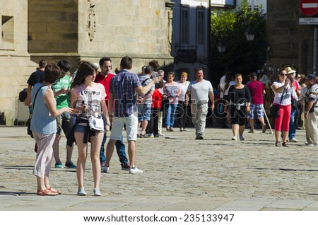 SANTIAGO DE COMPOSTELA, SPAIN - JULY 11, 2014: A group of tourists enjoying a sunny day at the Plaza de la Quintana in the historic city center. - stock photo