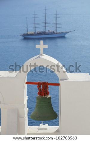 Santorini bell against big ship in Greece - stock photo