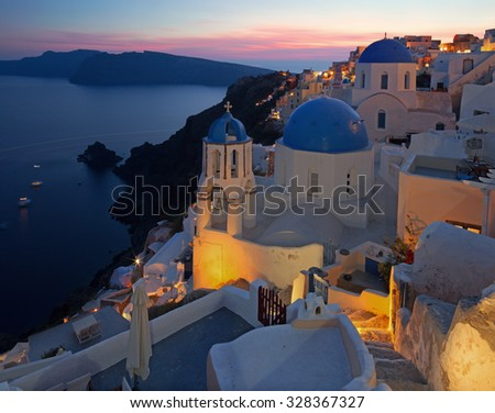 Santorini - The look to typically blue church cupolas in Oia over the caldera and the Therasia island in the background at sunset dusk. - stock photo