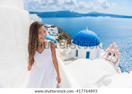 Santorini travel tourist woman on vacation in Oia walking on stairs. Person in white dress visiting the famous white village with the mediterranean sea and blue domes. Europe summer destination. - stock photo